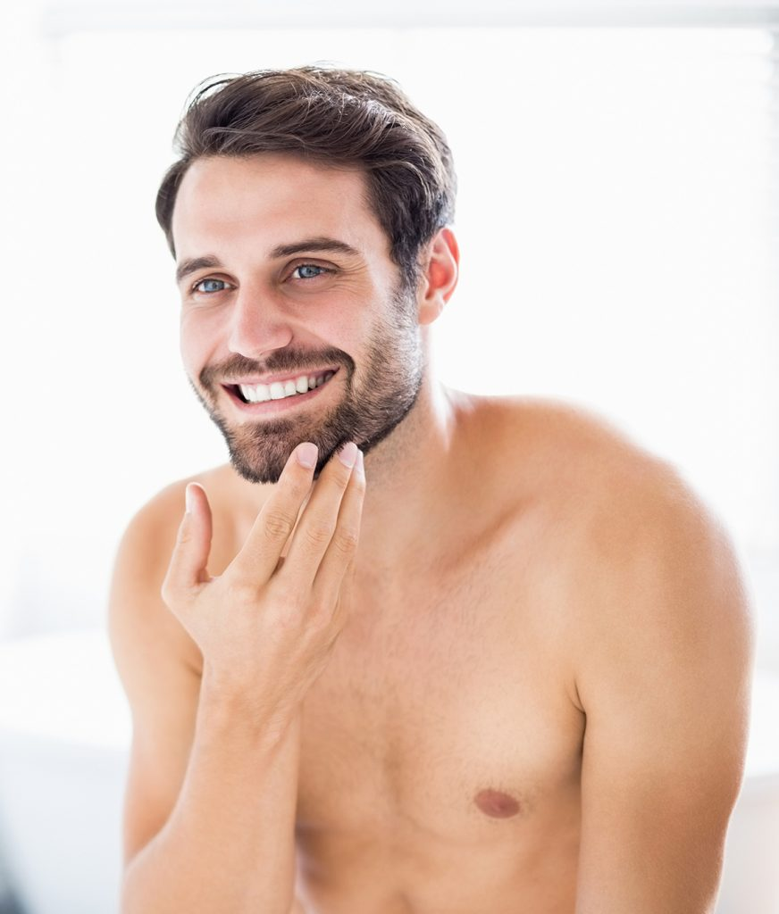 Bearded man touching his face