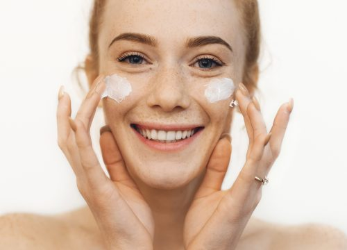 Woman with dry skin applying lotion to her face