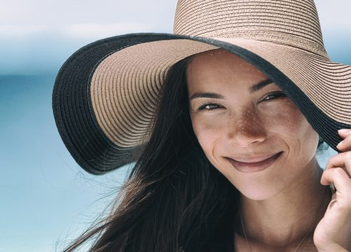 Woman wearing a hat at the beach to fight off sun damage