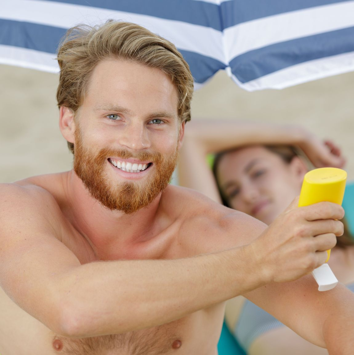 Man applying sun lotion at the beach
